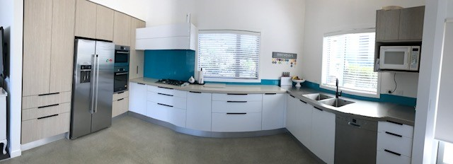 Blue, white, and wooden kitchen wide angle view.